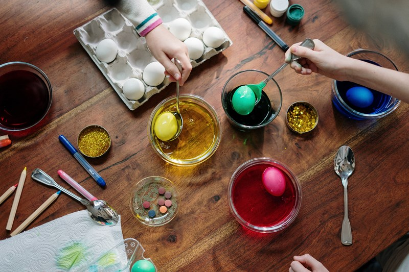 coloring_easter_eggs_with_supplies_on_the_table